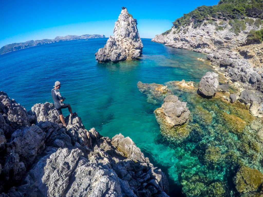 Man on the rocks coasteering in a beautiful cove in Mallorca